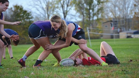 Kenyon student rugby players grapple over the ball
