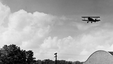 Men watch a biplane fly over the hangar at the Kenyon College School of Aeronautics.
