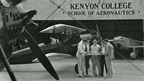 Students enrolled in Kenyon College's School of Aeronautics gather outside the hangar to look over flight plans.